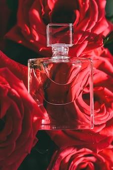 花の香りまたは香水と赤いバラの香水は、豪華なギフトの美しさのフラットレイの背景とコスとして...