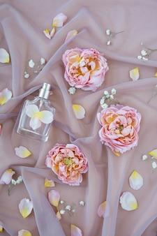 꽃 향기. 장미 꽃잎이있는 부드러운 핑크색 원단에 향수 스프레이 병