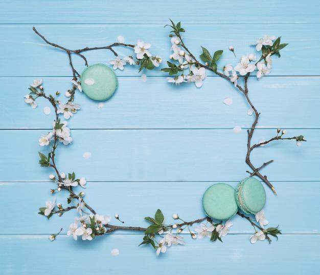 花のフレームと青い木製の背景にデザートマカロン