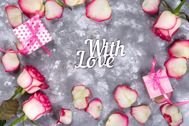 Floral frame: bouquet of pink white roses and gift boxes on stone background