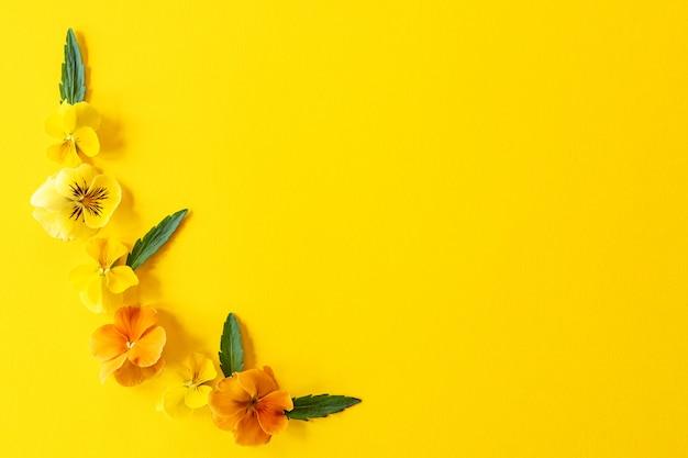 Цветочная рамка композиции. композиция из цветов анютины глазки на желтом фоне с копией пространства