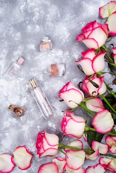 Floral frame composition with roses and many different perfume bottles on stone background.