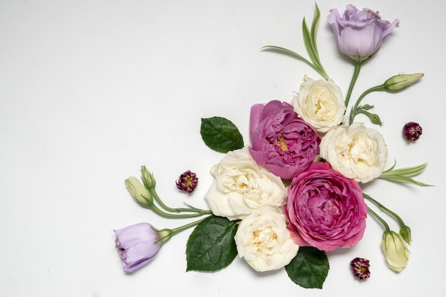 灰色の背景に花のフレーム。上面図とコピースペース。繊細なライラックのバラとトルコギキョウ。コーナー構成。高品質の写真