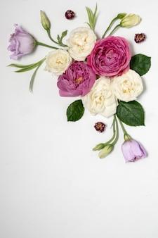 灰色の表面に花のフレーム。上面図とコピースペース。繊細なライラックのバラとトルコギキョウ。コーナー構成。高品質の写真