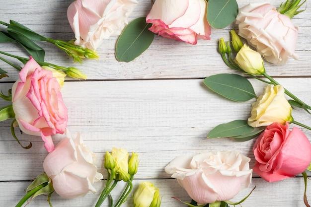 白い木製のぼろぼろの背景に花のフレーム。クリーミーなトルコギキョウ、ユーカリ、ピンクのバラ。休日のコンセプトとコピースペース