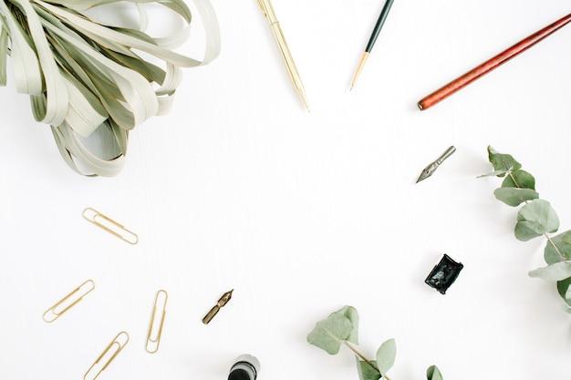 펜, 브러시, 유칼립투스 및 클립이있는 흰색 꽃 프레임