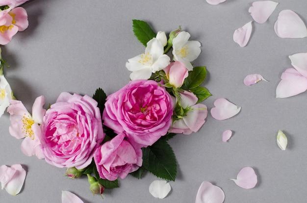 꽃 프레임. 회색 배경에 장미 꽃입니다. 평평하다
