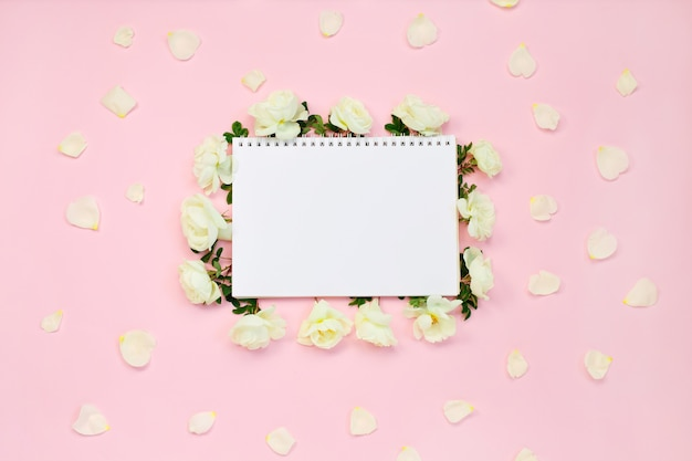 Floral frame of white roses and petals around notebook