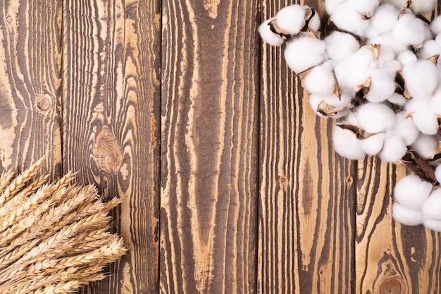 Цветочная рамка с цветами хлопка на фоне древесины с пшеницей. место для текста или фона