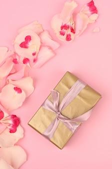 ピンクのスペースにゴールドのギフトボックスと花のフレーム。ご挨拶コンセプト