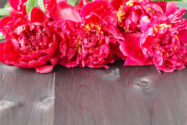 Floral frame with pink peonies on wooden