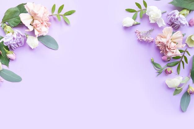 Цветочная рамка с розовыми розами, белыми цветами, ветвями, листьями и лепестками на фиолетовом фоне. плоская планировка, вид сверху