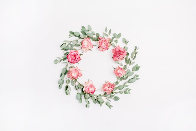 Floral frame wreath made of red rose flowers and eucalyptus branches isolated on white background. flat lay, top view