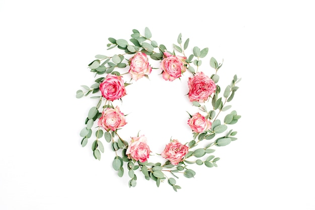 Floral frame wreath made of red rose flowers and eucalyptus branches on white background. flat lay, top view