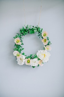 Floral frame wreath near pale blue wall