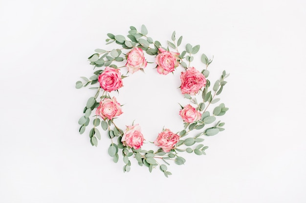 Floral frame wreath of red rose flowers and eucalyptus branches on white background. flat lay, top view