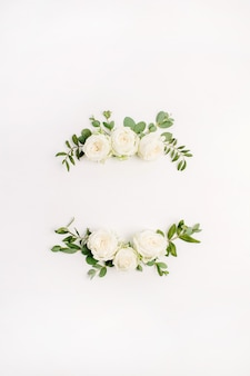 Floral frame wreath of white rose flower buds and eucalyptus on white