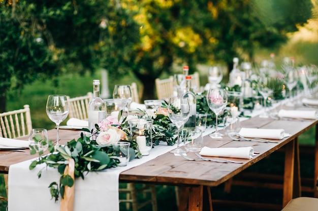 유칼립투스와 분홍색 꽃의 꽃 화관이 테이블에 놓여 있습니다.