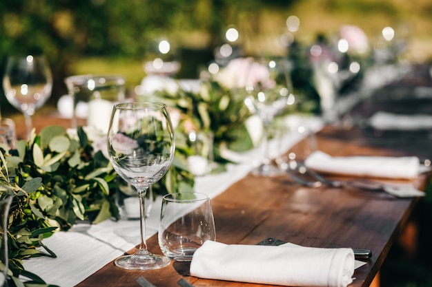 ユーカリの花輪は結婚式の夕食のテーブルにあります。