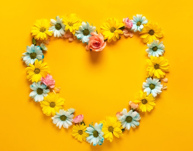 Floral heart-shaped wreath on yellow.