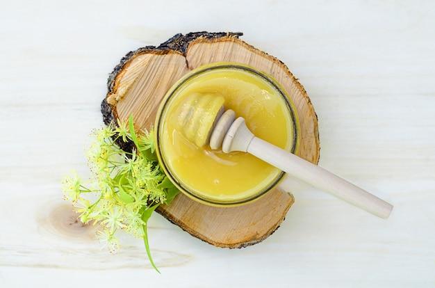 木製のテーブルにひしゃくと花のリンデン蜂蜜