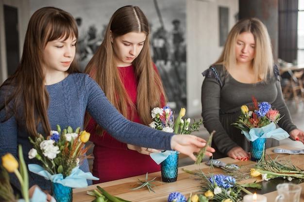 Цветочный мазер-класс. женщины делают цветочные композиции из живых цветов.