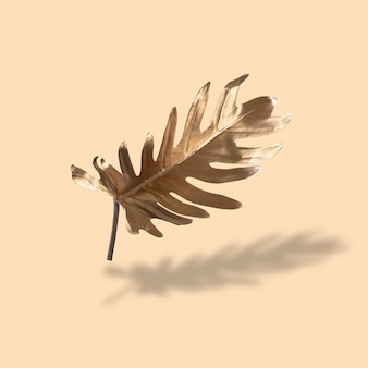 Floral minimalist style concept exotic summer trends golden tropical fern leaves on a pastel nude