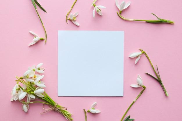 花のモックアップ空の紙の空白と淡いピンクの背景に繊細なスノードロップの花
