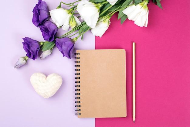 ノートブックと花のモックアップ。花とカラー紙の背景に空のノートブック。ピンクの背景に柔らかいトルコギキョウの花。コピースペース付きフラワーカード。