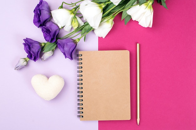 Floral mockup with notebook. flowers and empty notebook on color paper background. tender eustonia flowers on pink background. flowers card with copy space.