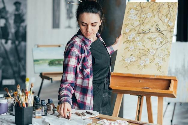 花柄のアートワーク。アーティストの才能とライフスタイル。ツールを選ぶ気配りのある若い女性。創造的なプロセス。