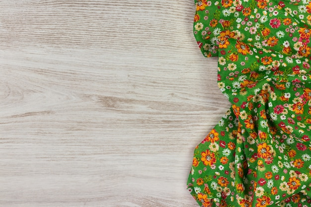 Floral pattern cloth napkin on white wooden background.