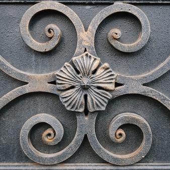 ラフな灰色の金属表面のクローズアップの花柄鍛造飾り。鋼のテクスチャの金属の花。原始的な花柄の古い鉄のパネル。ヴィンテージの彫刻が施された鉄のレリーフの背景。