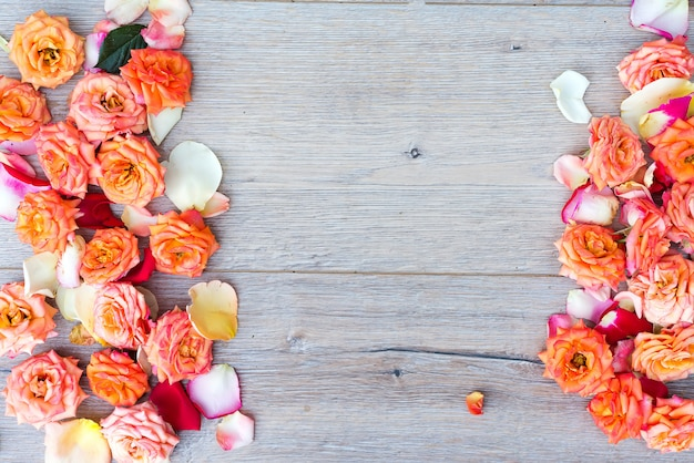 Floral pattern, frame made of roses on wooden background. flat lay, top view.