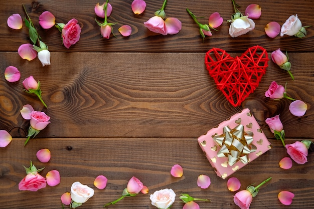 Floral pattern made of pink and beige roses, green leaves on wooden background.valentine's day background.