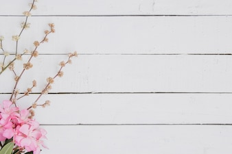 Floral pattern of light pink branches on wood background.