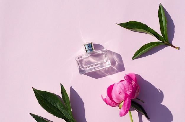 フローラル香水。ピンクの背景に牡丹の香りの香水のボトル