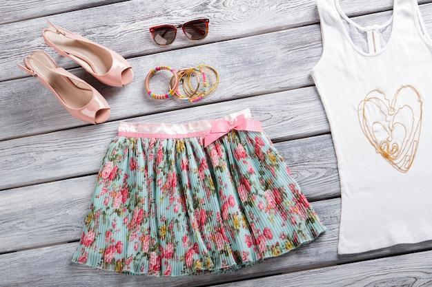 꽃무늬 스커트와 선글라스. 연어 신발과 흰색 탑. 테이블에 소녀의 세련된 팔찌. 고품질 의류 품목.