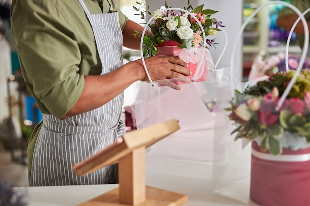 Floral specialist wearing an apron and brown shirt letting a pot with flowers down to a transparent package