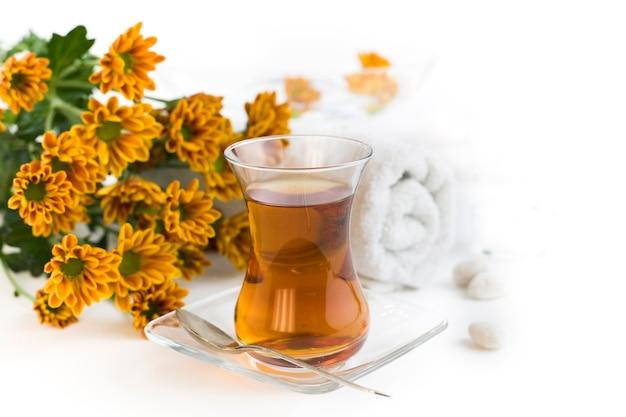 Цветочный чай в стакане и цветы