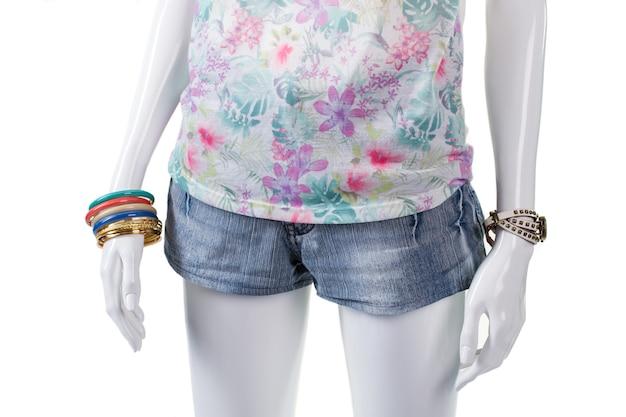 꽃무늬 탑과 손목 액세서리. 마네킹에 데님 미니 반바지. 여성용 작은 여름 반바지. 세련된 의류의 조합.