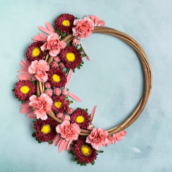 Floral wreath with carnations and daisies with copy space