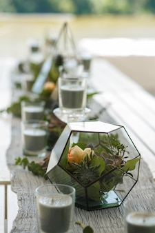 Florarium with fresh succulent and rose flowers festive table decoration.