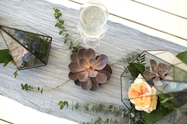 Florarium with fresh succulent and rose flowers festive table decoration