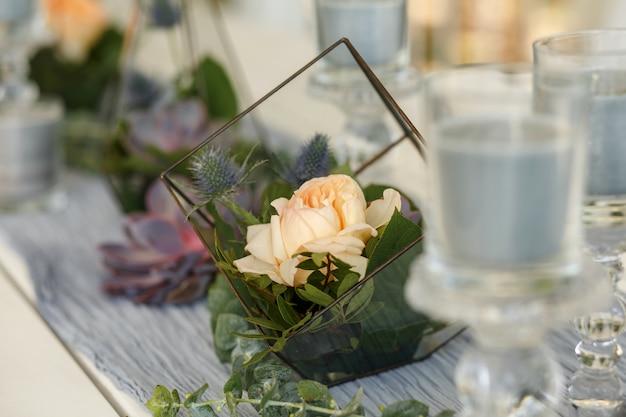新鮮な多肉植物とバラの花のお祝いテーブルデコレーションのflorarium。イベント生花装飾