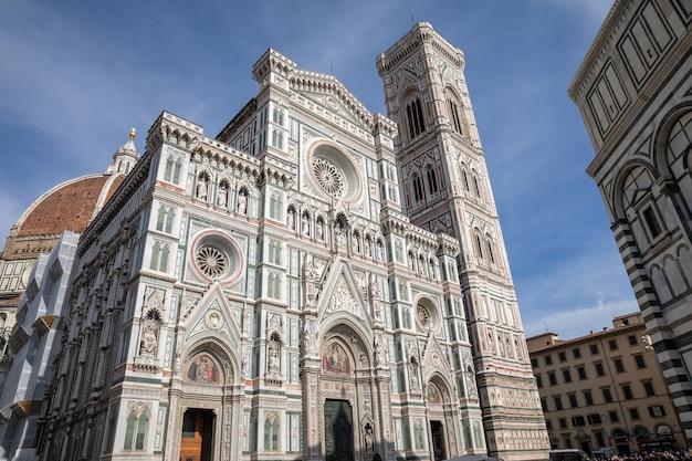 イタリア、フィレンツェ-2018年6月24日:サンタマリアデルフィオーレ大聖堂(花の聖マリア大聖堂)とジョットの鐘楼のパノラマビュー。人々は夏の日に広場を歩く