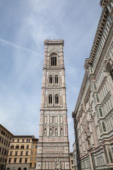 Флоренция, италия - 24 июня 2018: панорамный вид на колокольню джотто - колокольня, которая является частью собора флоренции на площади пьяцца дель дуомо. люди ходят по площади в летний день