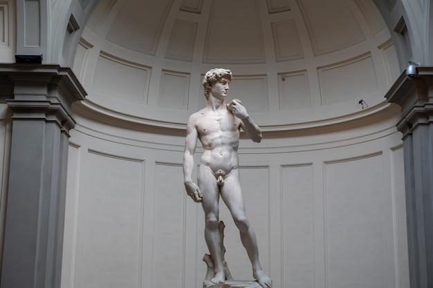 イタリア、フィレンツェ-2018年6月24日:彫刻のあるホールのパノラマビューは、フィレンツェの美術アカデミーで1501年から1504年の間に作成されたイタリアの芸術家ミケランジェロによるデビッドです