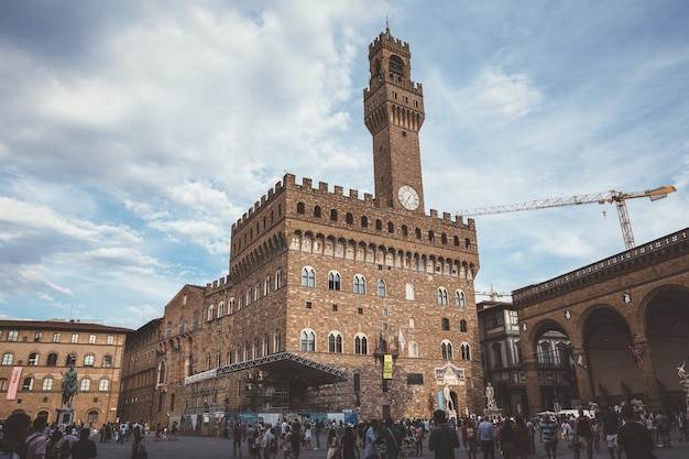 Florence, italy - june 24, 2018: panoramic view of palazzo vecchio (old palace) is the town hall of florence. people walk on piazza della signoria in summer day
