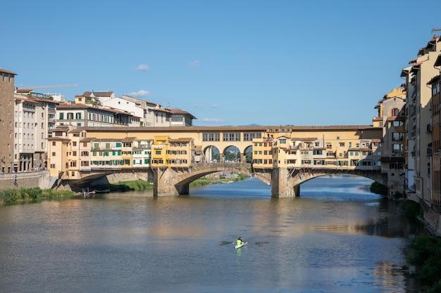 Флоренция, италия - 26 июня 2018: панорамный вид на понте веккьо (старый мост) - это средневековый каменный сегментный арочный мост с закрытыми перемычками через реку арно во флоренции. летний день и голубое небо